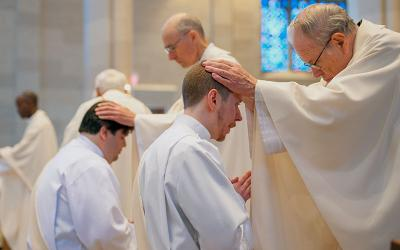 Priests lay their hands on the heads of Father's Jorge Ramírez (left) and Justin Miller during the priestly ordination June 4, 2016.