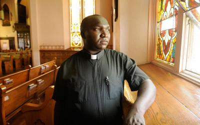 Father John Orenge Omboga, new parochial vicar for Our Lady of the Lakes Catholic Community, poses at Penn Yan's St. Michael Church July 17.