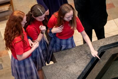 Students from St. Francis-St. Stephen School in Geneva dip their fingers in the baptismal font following the Catholic Schools Week Mass at Sacred Heart Cathedral.