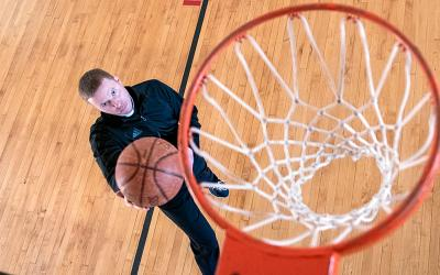 Father Justin Miller shoots a basket in the St. Hyacinth gym in Auburn.