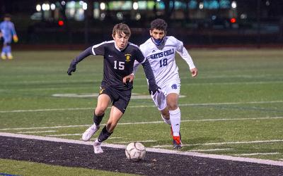 McQuaid Jesuit's Sam Colaprete chases the ball, followed by Gates-Chili's Mustafa Alshuaibi during the Section V Class AA Boys Soccer quarterfinal Nov. 13 in Brighton.