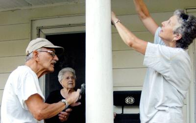 Kathy Peters (right) and Paul Wenderlich (left) scrape paint off of Yolanda Giansante's porch Aug. 15. Peters and Wenderlich belong to the new Local Missionary Group.