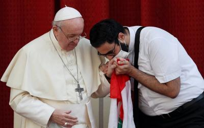 masked Maronite Father Georges Briedi kisses the hand of Pope Francis as the two men hold a Lebanese flag