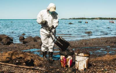 A volunteer in white suit cleans oil in Riviere des Creoles, Mauritius