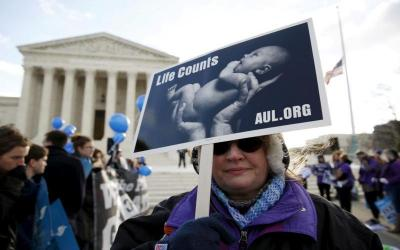 pro-life supporter holds up a sign in front of the U.S. Supreme Court