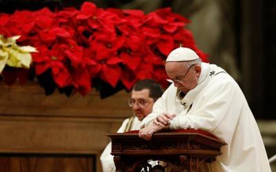 Pope Francis kneels in prayer