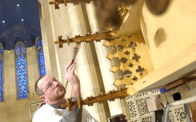 Ambrose Capps of Conrad Schmitt Studios varnishes the baldachin for the eucharistic chapel. (Courier photo by Mike Crupi)