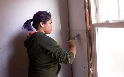 Ana H Martinez works to finish dry walling a section of the stairway at 228 Melville Street in Rochester on Nov. 26, 2019.as part of the City Roots Community Land Trust of Rochester.
