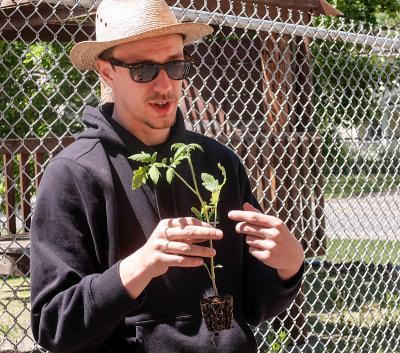 """Nathaniel Mich of Foodlink explains how to plant a tomato plant May 20 as part of The Cathedral Community's """"Adopt-a-Crop"""" program."""