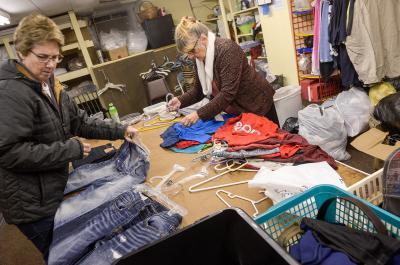 Diane Poole and Betty Jackson (above) sort clothes at Catholic Charities of Wayne County's Community Clothing Center in Wolcott Dec. 12 as Pam AuClair (right) bags items. The agency helps fund some of its ministries using Catholic Courier/Catholic Charities Christmas Appeal proceeds. (Courier photo by John Haeger)