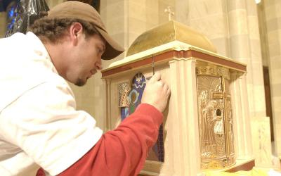 In early January, Mike Blanck, a decorator for Conrad Schmitt Studios, put finishing touches on the restored tabernacle. (Courier photo by Mike Crupi)