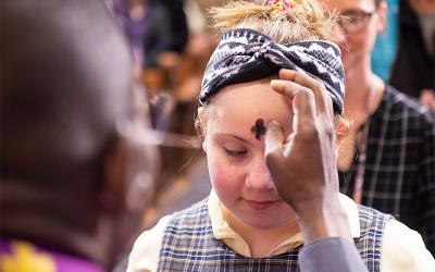 Fifth-grade student receives ashes from priest.