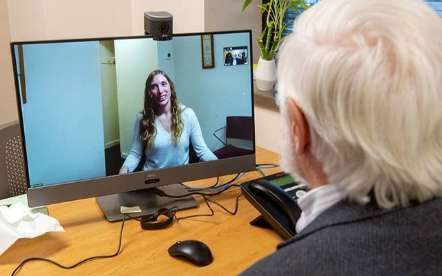 In 2019, Dr. Robert Young and Jessica Pruitt demonstrated the capabilities of Catholic Family Center's new telehealth service, which allows clients at the agency's clinics and residential treatment centers to see their providers remotely. (Courier file photo)