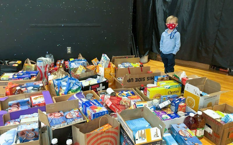 Liam Odenbach, a kindergartner at St. Rita School in Webster, stands with food that was donated during the school's celebration of Catholic Schools Week. (Photo courtesy of St. Rita School)