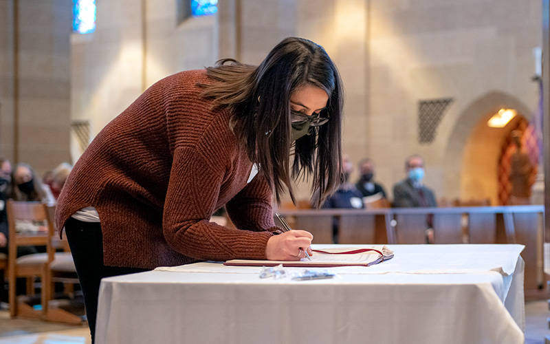 Catechumen Christina Ashbery from Holy Cross and Our Mother of Sorrows churches in Charlotte and Greece signs the Book of the Elect during the Feb. 21 Rite of Election and Call to Continuing Conversion ceremony at Sacred Heart Cathedral.