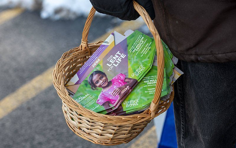 Catholic Relief Services Rice Bowl boxes are passed out during an Ash Wednesday drive-through at St. Monica Church in Rochester Feb. 17. (Courier photo by Jeff Witherow)