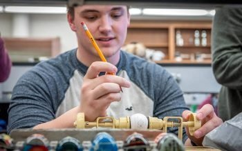"""Devan Rohrich, a senior at the University of Mary, decorates an Easter egg in the Slavic tradition during a March 24, 2021, class at the Bismarck, N.D., campus. The """"Pysanky Slavic Egg Design Course"""" is being offered during the spring semester to tie the ancient folk art and its spiritual aspects with the university's Catholic values. (CNS photo by Grace Ballalatak/courtesy University of Mary)"""