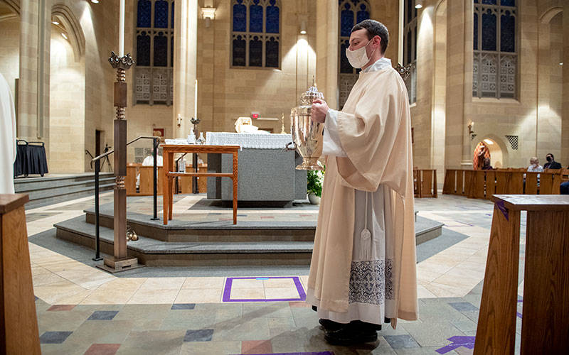 Deacon Joseph Maurici brings forward the Sacred Chrism during the Chrism Mass March 30. Deacon Maurici will be ordained a priest June 5.