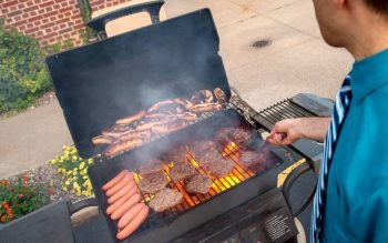 Burgers and hot dogs are prepared during a Grilling with God event at St. John the Evangelist Church in Rochester in 2018. (Courier file photo)