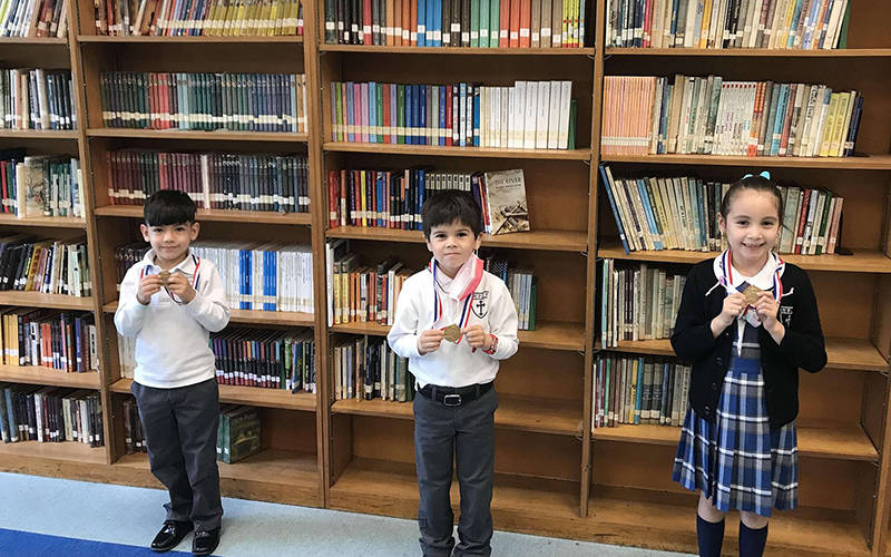 Holy Family Catholic Academy students from New York City show their handwriting medals for winning the state competition. From left are first graders Arron Morocho Kgn and Jake Mulryan, 2021 winners, and 2020 first-grade winner Isabella Ordonez. (CNS photo courtesy Diocese of Brooklyn)
