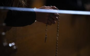 A woman recites the luminous mysteries of the rosary at the Basilica of the National Shrine of the Immaculate Conception in Washington in January. (CNS photo by Tyler Orsburn)