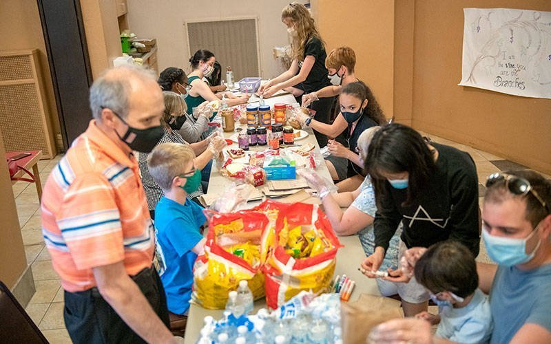 Volunteers at St. Monica Church in Rochester form an assembly line to make peanut butter and jelly sandwiches for Open Door Mission June 6. (Courier photo by Jeff Witherow)