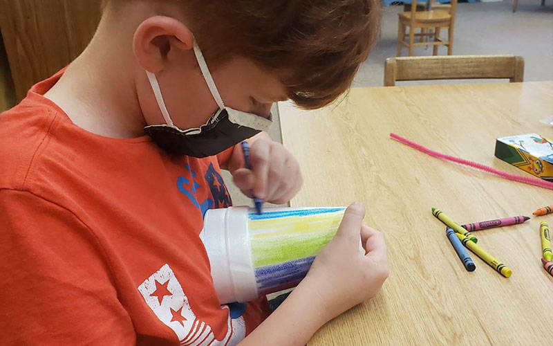 (A faith-formation student from Our Lady of the Valley Parish uses crayons to decorate a foam cup during Craft and Prayer night at St. Ann Church in Hornell June 13.
