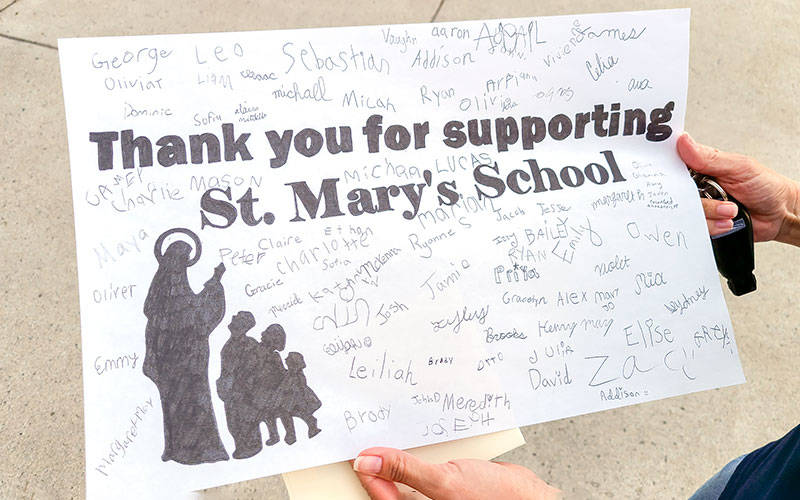 Parent-Teacher Organization member Kellie Parker holds up a poster signed by St. Mary School students that was given to Mac's Philly Steaks on Main Street in Canandaigua as appreciation for a May 18 fundraiser to benefit the school. (Courier photo by Jeff Witherow)