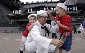 A sailor aboard the USS Constellation in San Diego is greeted by his children in this 2003 file photo. The invitation to move outside of the self to the other is the divine pedagogy of fatherhood. (CNS photo by Jaime Recto/Reuters)