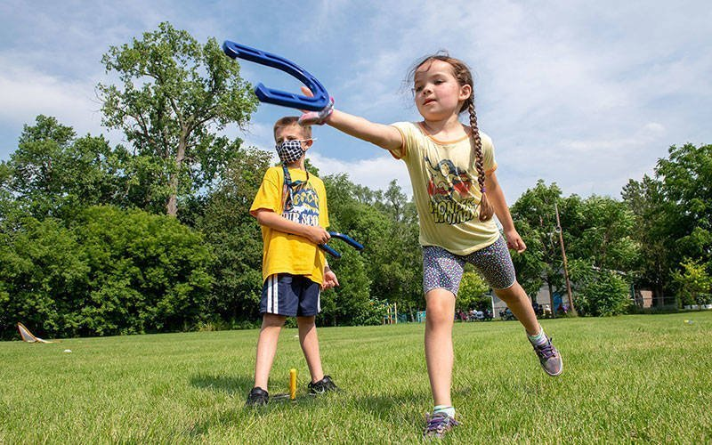 Joey Russel (left) watches Willamena Avellaneda (right) throw her horseshoe during the June 21 field day at St. Michael School in Penn Yan.
