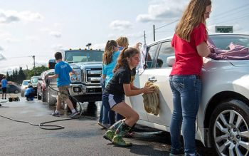 Members of the youth groups at St. Charles Borromeo and St. Mark churches in Greece wash cars Sept. 10 to raise funds for their trip to the National Catholic Youth Conference in November.
