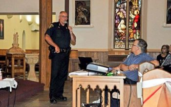 <p>Monroe County Sheriff Todd Baxter speaks at Holy Cross Church in Rochester July 26.</p>