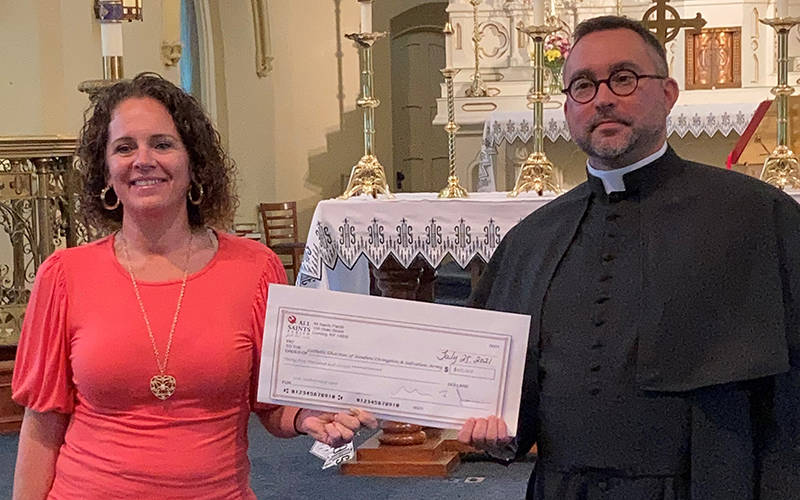 Father Matthew Jones, pastor of All Saints Parish in Corning, presents a check to Tessa Schove, social services manager with the Salvation Army in Corning. Through a Lenten fundraising effort, the parish raised nearly $35,000 to help local charities aid residents affected by the COVID-19 pandemic. (Photo courtesy of All Saints Parish)