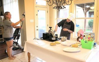 """Becky Delatte, a parishioner of Divine Mercy Church in Kenner, La., films a Facebook Live segment in which her pastor, Father Robert Cooper, and her 4-year-old daughter, Lucy, make """"Monstrance Waffles."""" (CNS photo by Beth Donze/Clarion Herald)"""