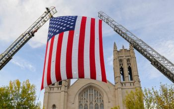 A flag hangs from fire truck ladders during a Sept. 11, 2009, Mass for firefighters and first responders at Rochester's Sacred Heart Cathedral. (Courier file photo)