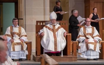 Deacons Brian Mizzoni (left) and Aaron Kelly (right) sit beside Bishop Salvatore R. Matano during the Aug. 21 diaconal ordination at Rochester's Sacred Heart Cathedral. (Courier photo by Jeff Witherow)