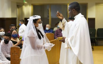 Andrea Ramirez, 11, receives Communion from Father Patrick Ojiakor Aug. 14, 2021, at St. John of God Church in Central Islip, N.Y. (CNS photo by Gregory A. Shemitz)