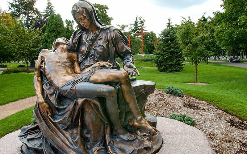 A bronze statue depicts the Blessed Virgin Mary cradling the dead body of Christ after his crucifixion.