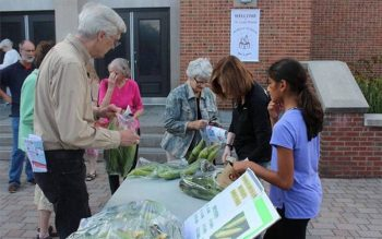 Children and adults gather around a table that is filled with bags of corn on the cob. Parishioners of St. Louis Church in Pittsford organize a corn sale each year to raise money for a pediatric hospital in Haiti. This photo is from the 2019 corn sale. (Photo courtesy of St. Louis Church)