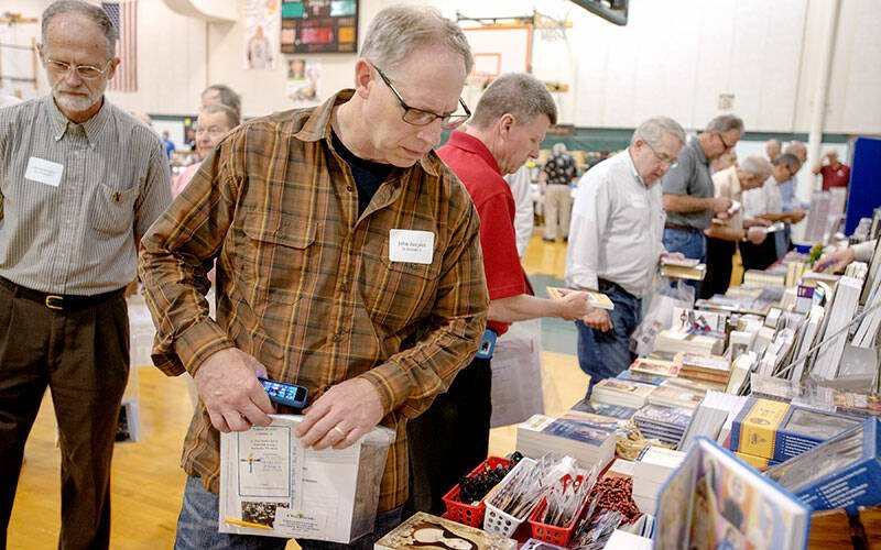 John Zaepfel browses books at a vendor stand at the first-annual ExultRochester Catholic Men's Conference at St. Jude the Apostle Church May 16, 2015. (Courier file photo)