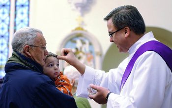 Deacon Peter Dohr places ashes on the forehead of 3-year-old Quinn Dale as Quinn's grandfather, Gary Brundage, looks on during an Ash Wednesday service at St. Rose Church in Lima, N.Y., Feb. 13, 2013. (CNS photo by Mike Crupi/Catholic Courier)