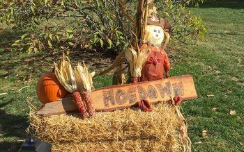 A scarecrow, pumpkin and ears of corn decorate a bale of hay. (Photo courtesy of Catholic Charities of the Finger Lakes)