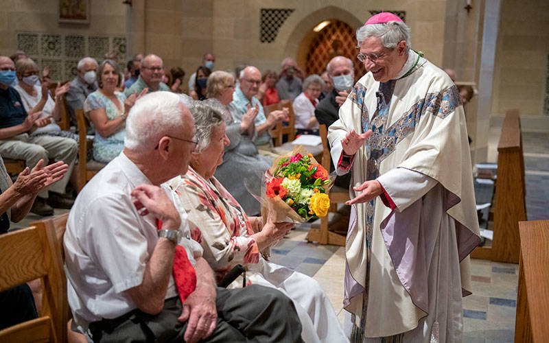 Bishop Salvatore R. Matano gives flowers to William and Athalene Fisher of St. Mary Church in Dansville. The Fishers, who have been married 70 years, were the longest-married couple to attend the Mass.