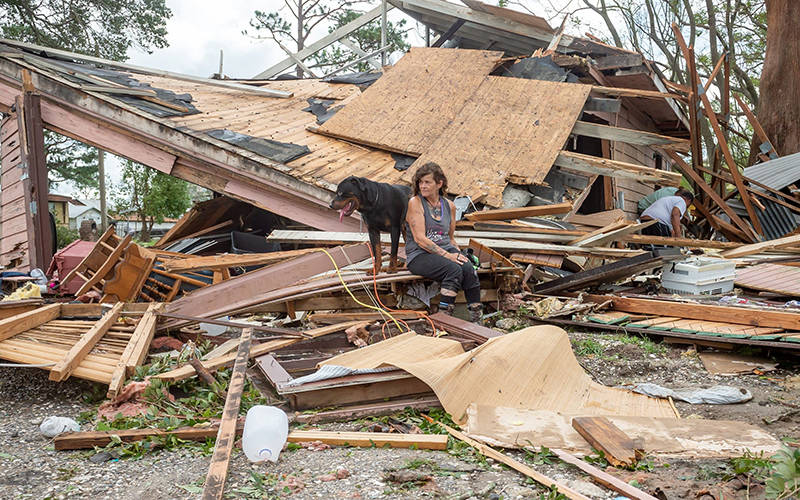 Fran Tribe sits with her dog, Dave, outside a home in Houma, La., Aug. 30, 2021, after Hurricane Ida made landfall. (CNS photo by Scott Clause/USA TODAY Network via Reuters)