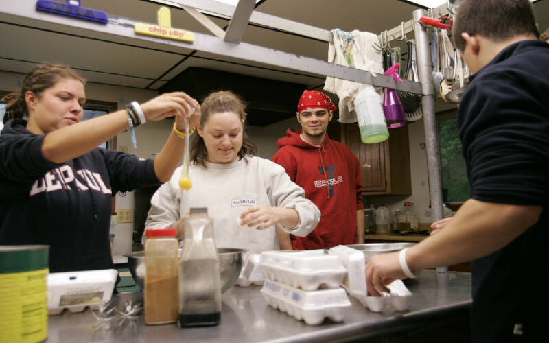 Teens and adults are in a kitchen cracking eggs into bowls. In this 2005 file photo, Meghan Blake from St. Michael Parish in Wheaton, Ill., breaks an egg as Kristi McHugh, a youth minister from St. Mary of Gostyn Parish in Downers Grove, Ill., and other volunteers help make breakfast at Nazareth Farm in Salem, W.Va. Our communication of Catholic social teaching should be hands on. (CNS photo by Paul Haring)