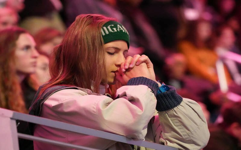 A teenage girl with long hair held back by a headband is leaning on a railing in an auditorium as she closes her eyes and folds her hands in prayer. A teenager prays during a pro-life youth Mass at Capital One Arena in Washington Jan. 24, 2020. Hopefully, by the time they are teens, our kids have seen how much we love Jesus and value being part of the Catholic Church. (CNS photo by Gregory A. Shemitz)