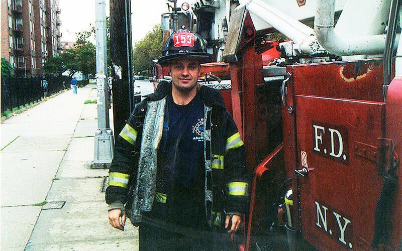 Stephen Siller is pictured in his FDNY fireman's uniform standing by a fire engine on a New York City street May 3, 2001. Siller died working to save others after the 9/11 terrorist attack on New York City. His brother, Frank, and his other siblings founded the Tunnel to Towers Foundation in his memory. (CNS photo courtesy Tunnel to Towers Foundation)