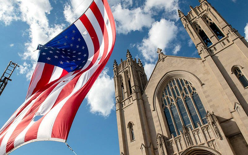 An American flag flies between two fire trucks in front of Rochester's Sacred Heart Cathedral Sept. 11 during a Mass recognizing first responders on the 20th anniversary of the Sept. 11, 2001, terrorist attacks on the U.S. (Courier photo by Jeff Witherow)