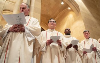 Fathers Lance Gonyo (from left), Edison Tayag, Stephen Karani and Frank Lioi stand for the Renewal of Priestly Promises during the April 16, 2019, Chrism Mass in Rochester. (Courier file photo)