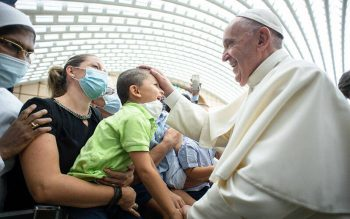 Pope Francis greets a child during an audience at the Vatican Sept. 18. The pope is scheduled to formally open the XVI Ordinary General Assembly of the Synod of Bishops at the Vatican Oct. 9-10.